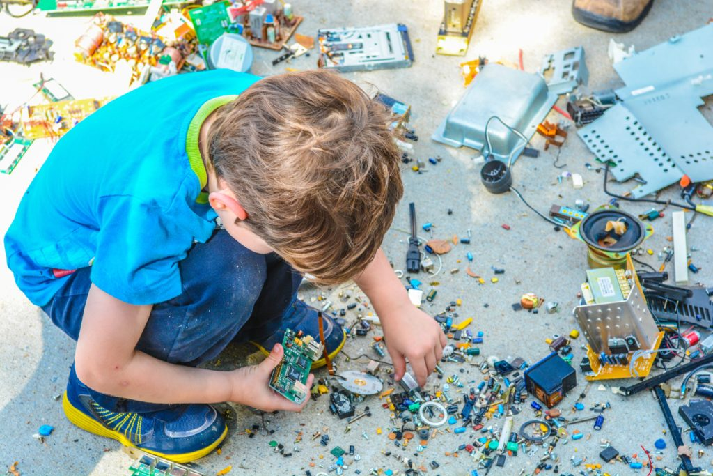 Photograph of a young child building something with assorted lego parts