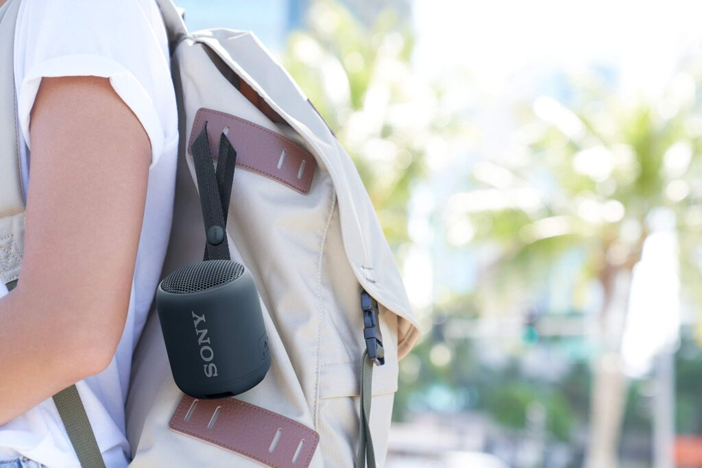 Sony SRS-XB12 Bluetooth speaker clipped onto a bag