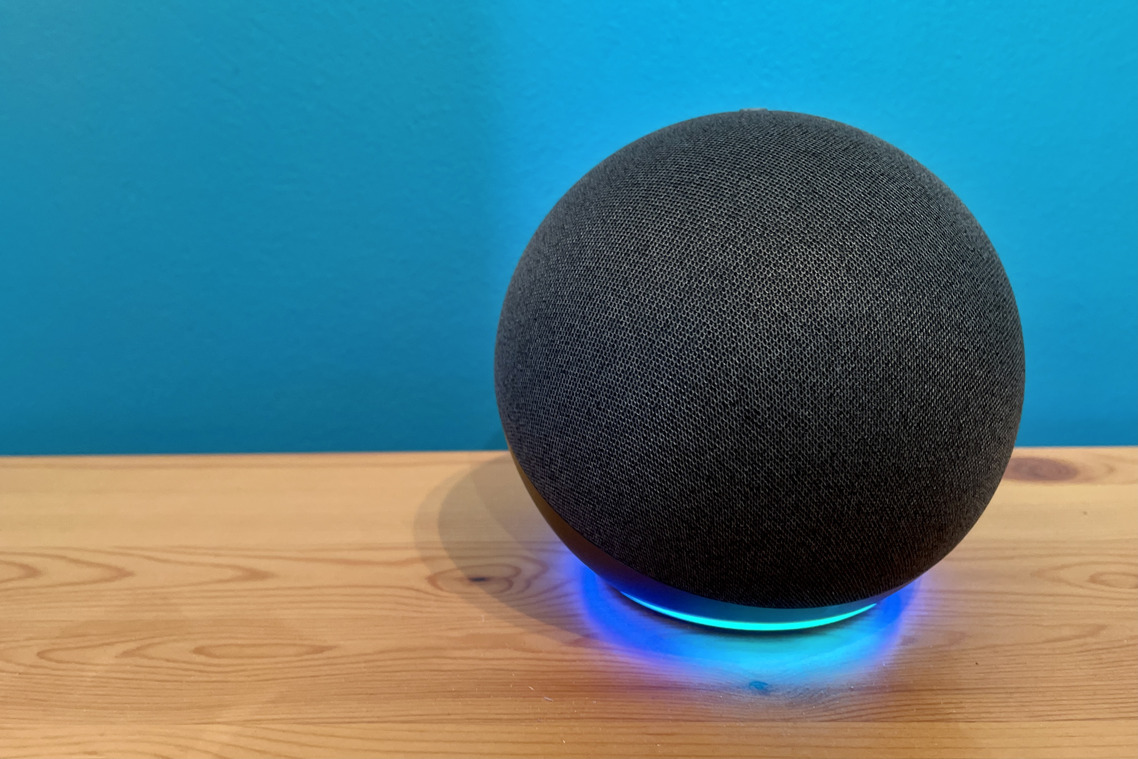 Amazon Echo on a wooden table against a blue wall