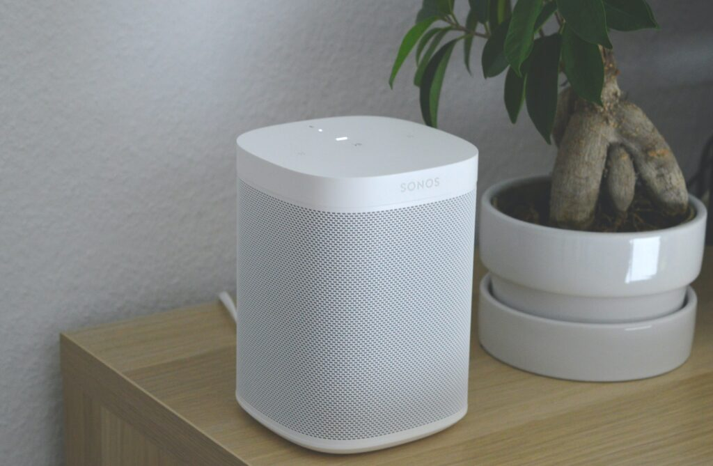 a white Sonos One smart speaker on a wooden table