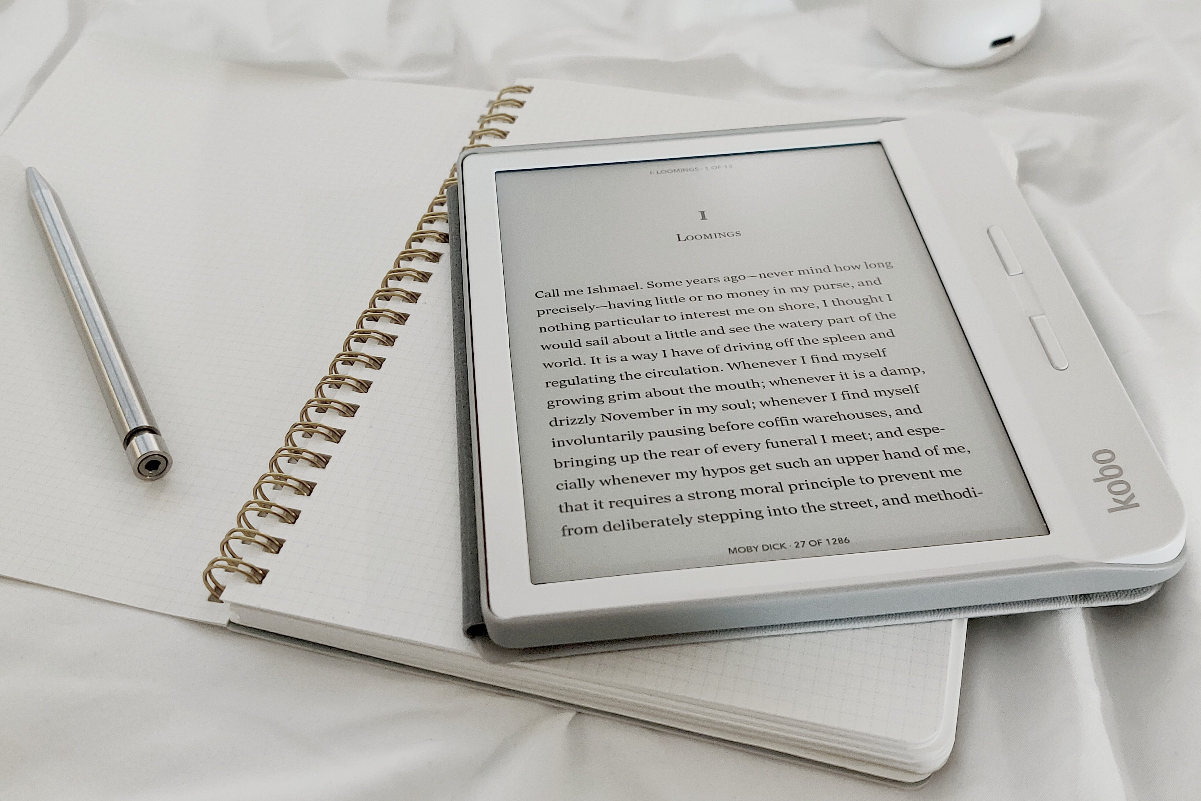 white ereader on top of a notebook